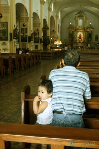 "What am I doing here? - The Vigan City Church is one of the oldest ever built by the Spaniards in the Philippines. Here, a father prays while the son waits as if saying ""what am I doing here""?"