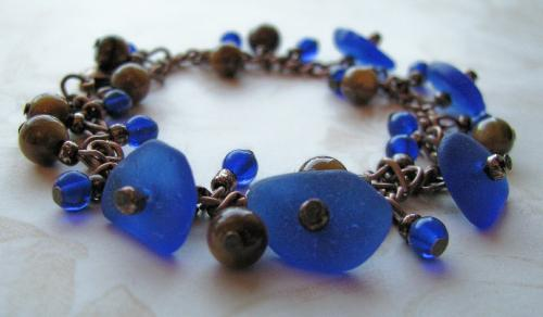 "Un-named sea glass bracelet - 5 authentic pieces of cobalt blue sea glass are the centerpieces of this copper 7 1/2"" bracelet. Cobalt sea glass is classified as a rare color."