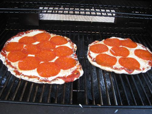 Grilled pizza - Two pizzas cooking on the grill.