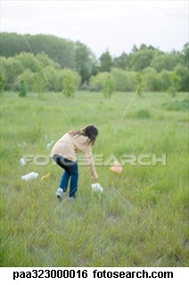 awareness - a women picking up the plastics from the park