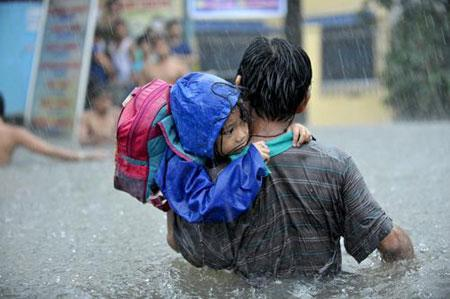 Typhoon Ondoy Aftermath - a man and a young child tries to wade their way through a very flooded street