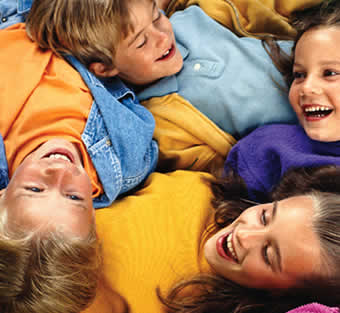 Kids - Picture of kids smiling and laying in bed to have a picture.