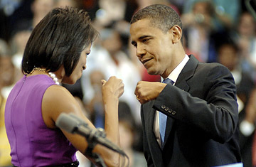 we're not telling... - Obama and Michelle Obama at podium doing fist bump, Michelle in purple dress, Obama black suit