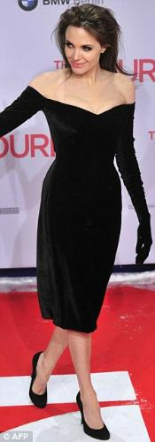 "Gloved Versace Dress of Angelina Jolie - Wearing a velvet, off-the-shoulder dress that hugged her curves, Jolie beamed as she posed for photos during the Berlin premiere of her movie with Johnny Depp, ""The Tourist""."